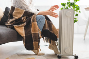 cropped view of girl with blanket warming up with heater in cold room - Best Portable Space Heaters of 2021