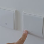 Hand switching on the light with the best smart home dimmer switch
